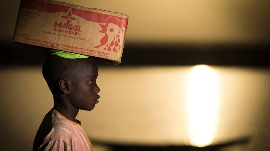 Menino carrega uma caixa em sua cabeça próximo ao rio Níger, em Gao, no Mali