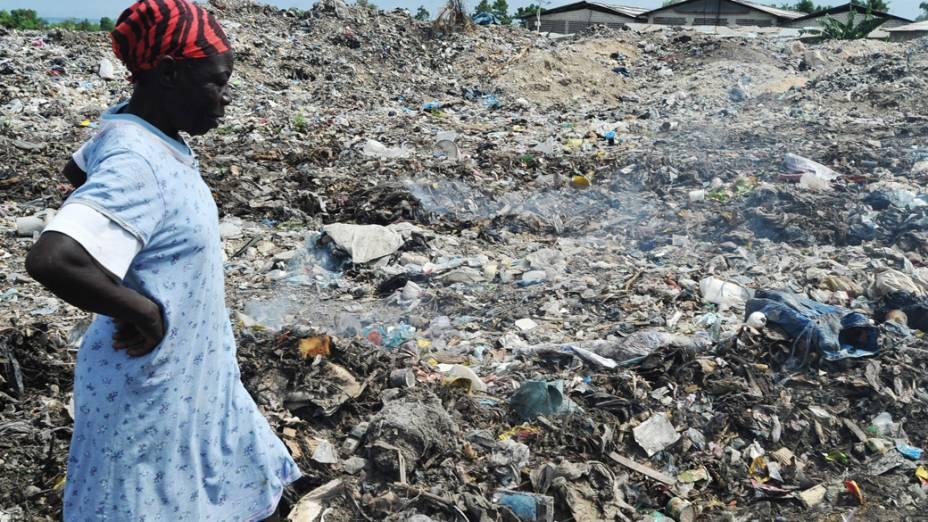 Mulher procura objeto para reciclar em um lixão no Haiti