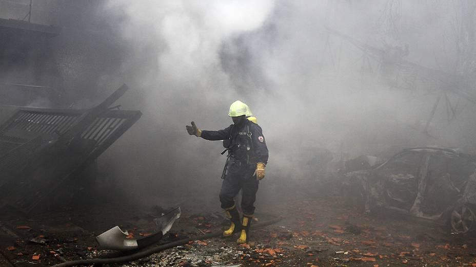 Bombeiro auxilia sua equipe onde carro-bomba explodiu no centro de Damasco, Síria