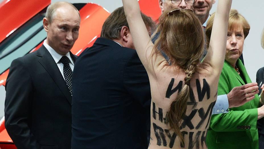 Manifestante de topless caminha em direção ao presidente russo, Vladimir Putin e a chanceler alemã, Angela Merkel durante visita ao industrial Hanover Fair, em Hanover, Alemanha