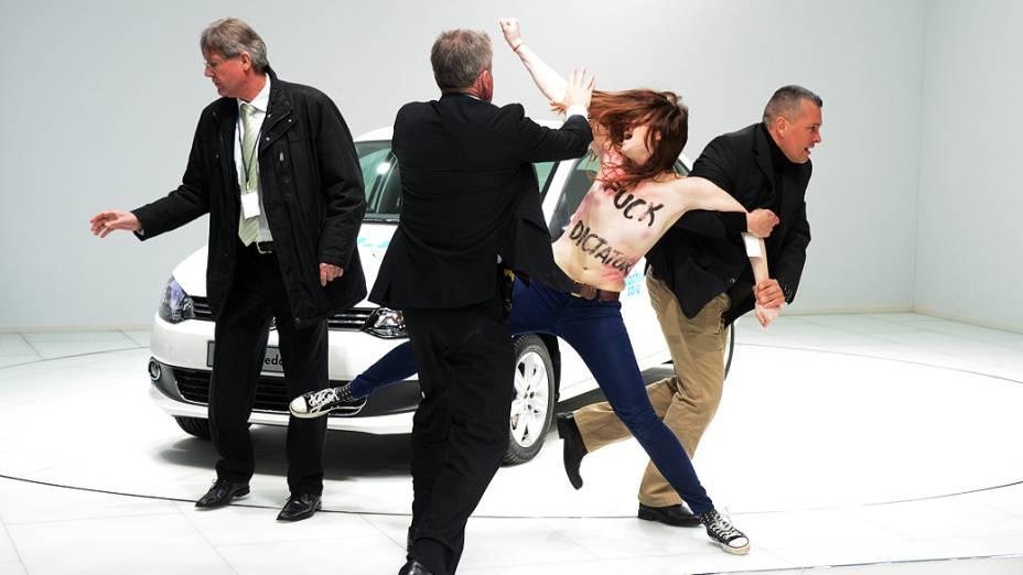 Manifestante de topless é retirada pelas forças de segurança durante a HanoverFair, na Alemanha