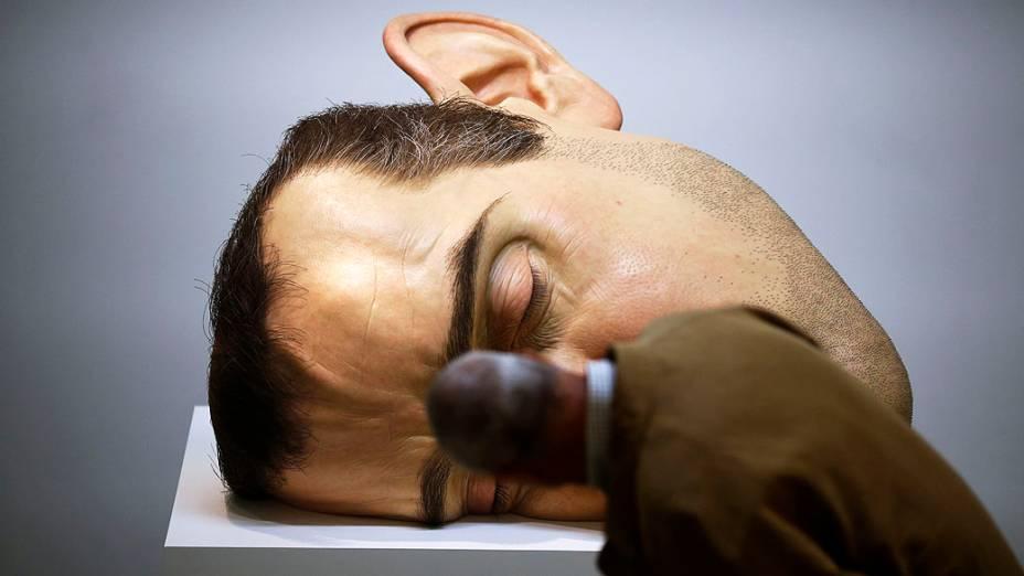 VIsitante observa Máscara II, escultura do artista australiano Ron Mueck exibida na Fundação Cartier, na França