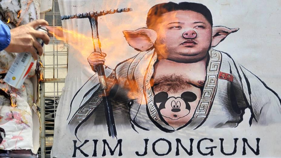 Ativista sul-coreano queima caricatura do líder norte-coreano Kim Jong-Un, durante um comício anti-Coreia do Norte, em Seul