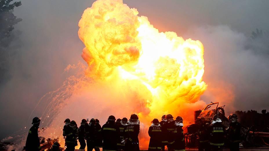 Bombeiros trabalham para apagar um incêndio após uma colisão entre um caminhão e outro veículo em uma estrada em Wuhan, província de Hubei, centro da China