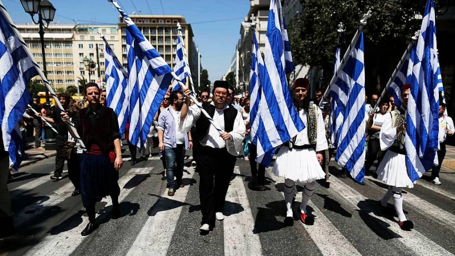 Trabalhadores municipais se vestem com trajes tradicionais durante protesto contra planos de demissões de milhares de trabalhadores do setor público, como parte de programa de reformas de austeridade, em Atenas, na Grécia