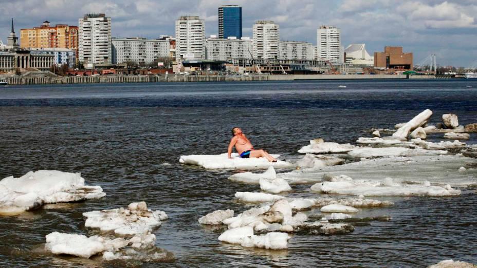 Homem toma sol sobre uma placa de gelo no rio Yenisei, na Rússia