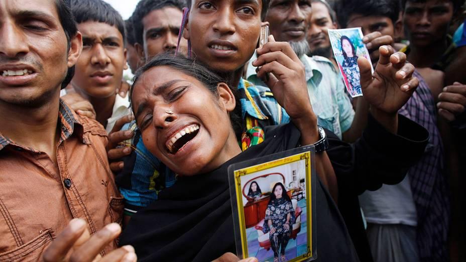 Parentes de uma costureira, desaparecida após o desabamento do edifício Rana Plaza em Savar, choram antes de um enterro em massa na cidade de Dhaka, Bangladesh