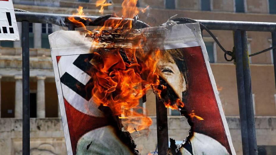 Cartaz com a foto da chanceler alemã, Angela Merkel vestindo um uniforme nazista é incendiado por um manifestante em frente ao parlamento grego na Praça Syntagma, em Atenas