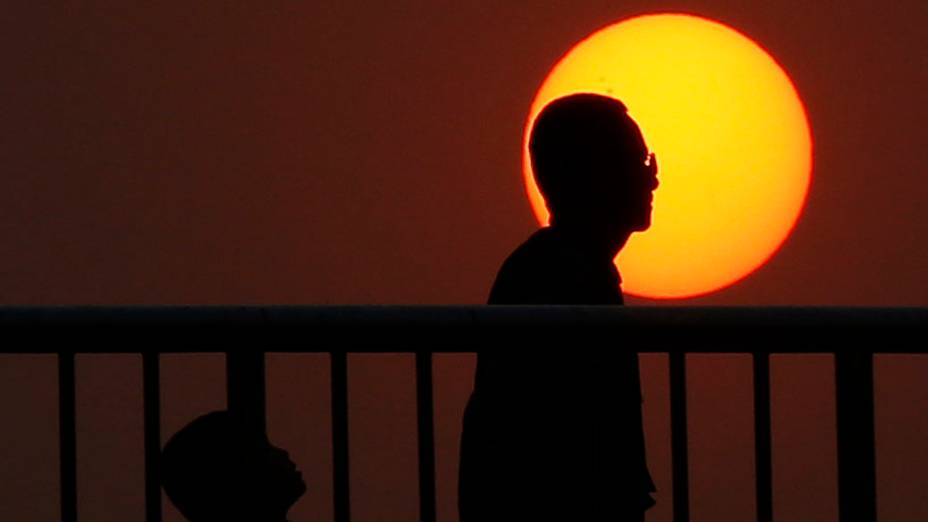 Pessoas são vistas durante pôr do sol em Pequim, na China