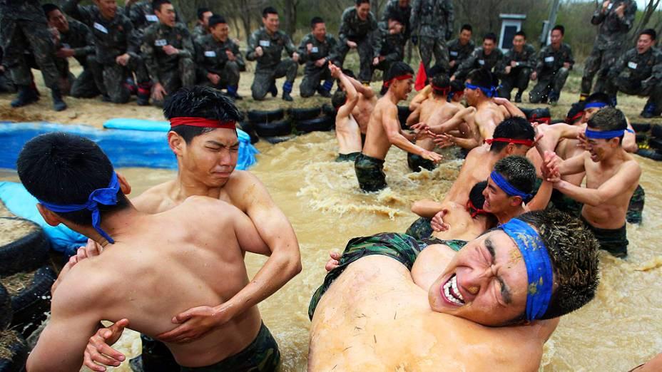 Membros das forças especiais sul-coreanas lutam em uma piscina de lama durante um exercício militar em Yeongcheon, a sudeste de Seul