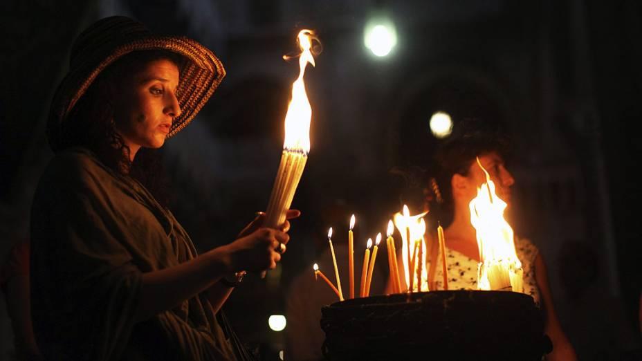 Em Jerusalém, mulher acende velas nas celebrações da Páscoa ortodoxa