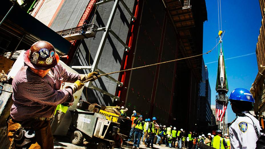 Trabalhador usa uma linha para firmar a peça final de um pináculo com a bandeira dos Estados Unidos antes de ser colocada no topo do One World Trade Center, em Nova York
