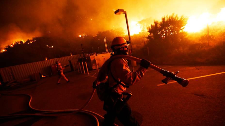Bombeiros lutam para proteger uma estação de manutenção perto Pacific Coast Highway, em Malibu, na Califórnia