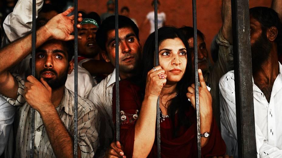Pessoas inclinam-se em uma cerca para ouvir o ex-primeiro-ministro falando em um comício de encerramento de campanha em Lahore, dois dias antes das eleições para a câmara baixa do parlamento e quatro assembléias, no Paquistão