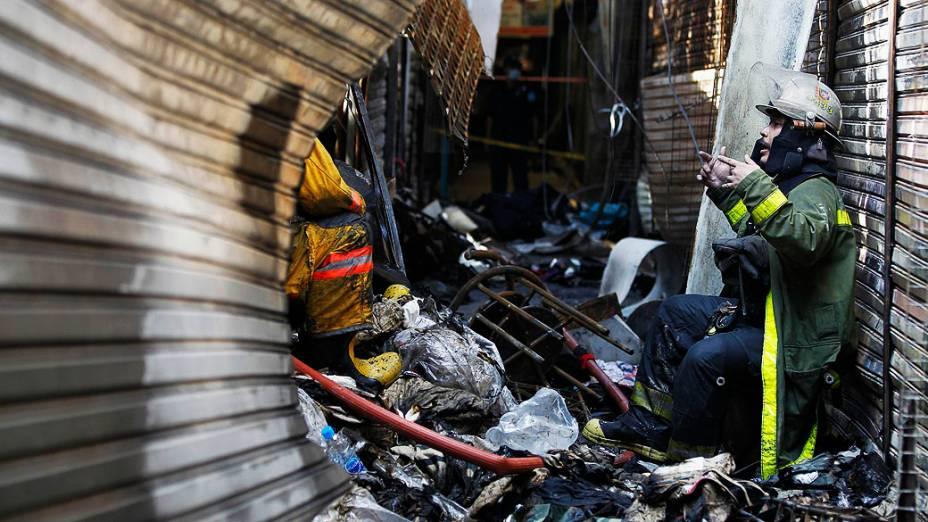 Bombeiro atende local ondevinte lojas foram destruídas após um incêndio a partir de um curto-circuito na seção de moda no famoso Mercado Chatuchak, em Bangcoc, Tailândia