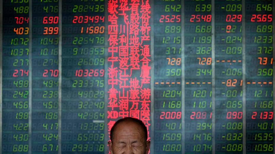 Investidor reage em frente de um painel eletrônico que mostra informações sobre ações em uma corretora em Taiyuan, na China