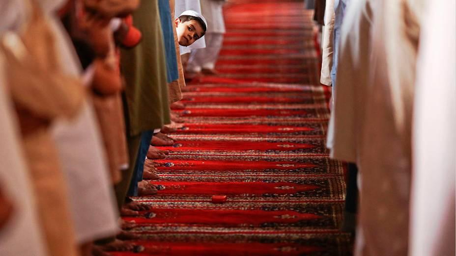 Menino observa orações da sexta-feira na mesquita de Wazir Khan, em Lahore, no Paquistão