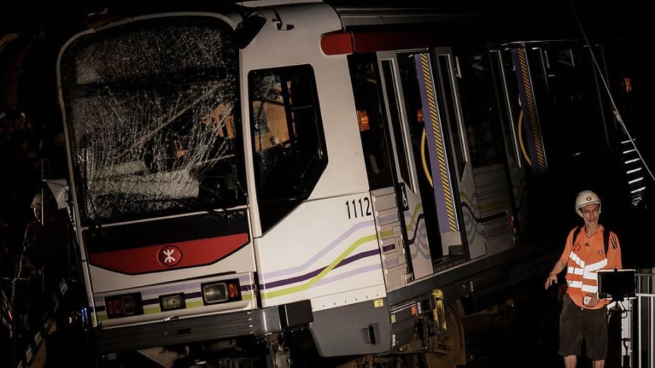 Trabalhador passa por um trem que descarrilou em Hong Kong. Sessenta e duas pessoas ficaram feridas quando vários carros descarrilaram na estrada de ferro luz de Hong Kong