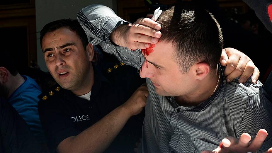 Policial ajuda homem ferido durante confrontos em um Dia Internacional Contra a Homofobia e Transfobia, na Geórgia