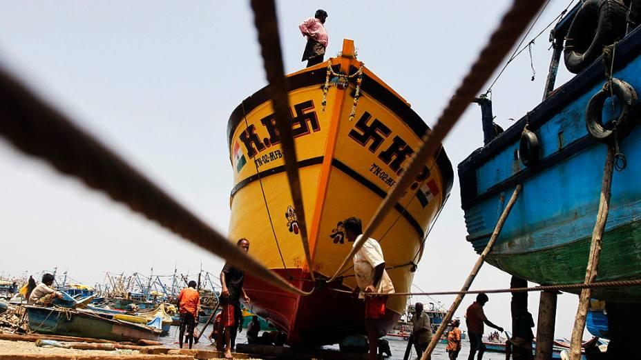 Pescadores preparam um navio de pesca antes de dirigir-lo nas águas da Baía de Bengala em um porto no sul da cidade de Chennai, Índia