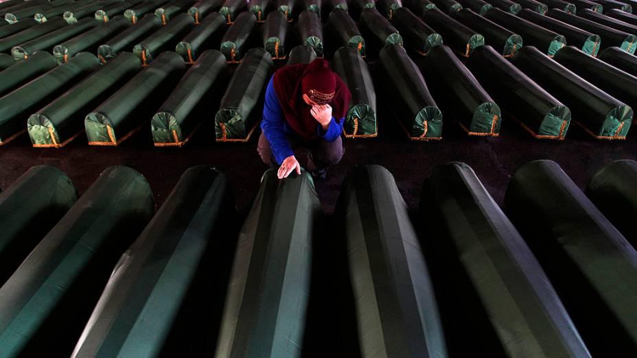 Mulher chora perto do caixão de seu parente, um dos 409 caixões de vítimas recém-identificadas do massacre de Srebrenica 1995, nesta quarta-feira (10), no Memorial Center Potocari. Os corpos das vítimas serão transportados para o centro memorial de Potocari, onde serão enterrados, marcando o 18 º aniversário do massacre em que as forças servo-bósnias comandadas por Ratko Mladic mataram cerca de 8.000 homens muçulmanos