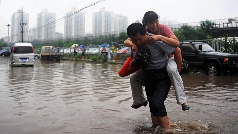 Homem carrega uma mulher em uma área alagada nesta terça-feira (16), em Pequim. Pelo menos 295 pessoas foram mortas ou desaparecidas após chuvas e o Tufão Soulik atingir a China