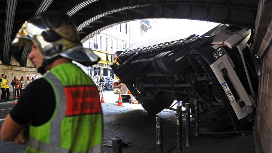 Bombeiro fica ao lado de um caminhão que caiu em uma vitrine, nesta terça-feira (16), em Marselha, França