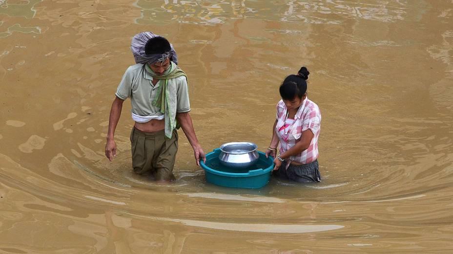 Residentes transportam água potável em um balde pela enchente, depois da chuva de monção atingir Dimapur nesta quarta-feira (17), em Nagaland. Centenas de pessoas ficaram desabrigadas durante as fortes chuvas de monções, que continuam atingindo a Índia