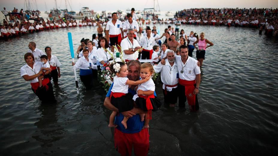 Homem segura seus filhos vestidos com trajes tradicionais enquanto a estátua da Virgem El Carmen é levada para o mar nesta quarta-feira (17), durante uma procissão em Málaga, na Espanha