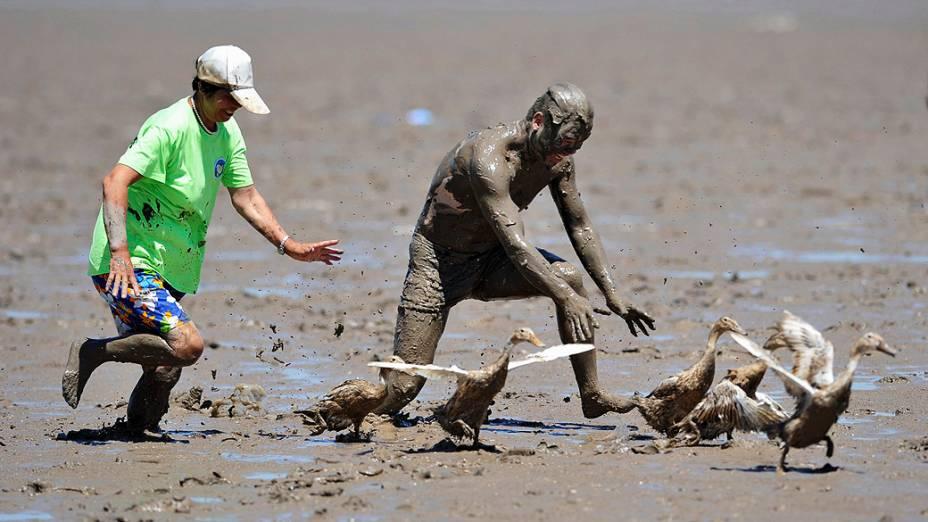 Participantes tentam apanhar patos em um campo enlameado, durante Carnaval na lama nesta quarta-feira (17), em um parque em Daishan, na China