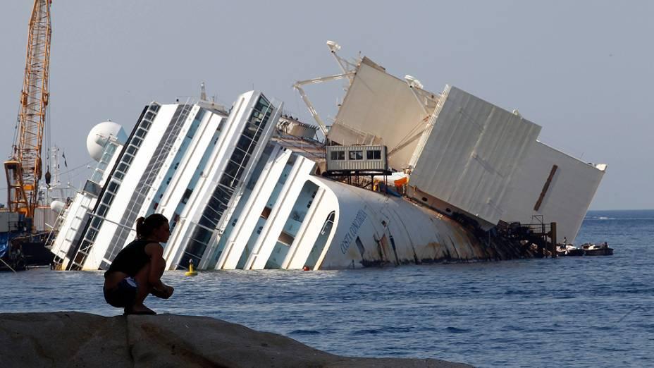 Banhista observa o navio Costa Concordia, que permanece há um ano e meio tombado à beira da ilha de Giglio, na Itália. Julgamento de Francesco Schettino começou nesta quarta (17) . Ele é acusado pelo naufrágio que matou 32 na costa italiana em 2012