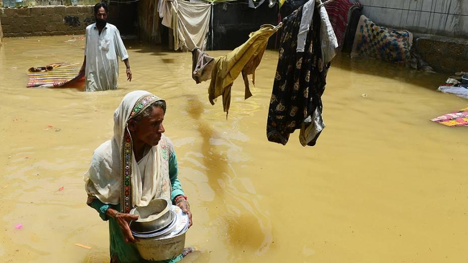 Mulher em casa inundada após chuva em Karachi, no Paquistão