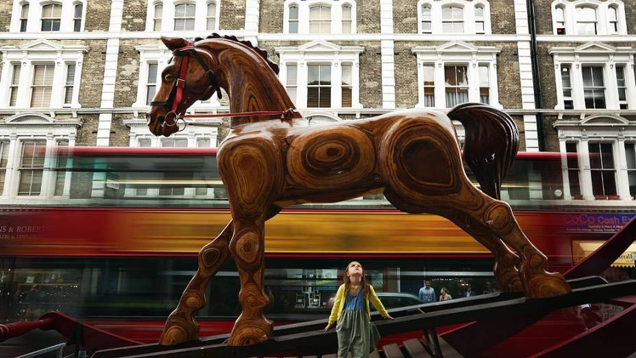 Criança senta em uma cadeira balanço gigante em forma de cavalo fora de Christie Auction House, em Londres, Inglaterra. O cavalo faz parte do Out of the Ordinarye sua venda deverá render entre 25 e 40 mil libras