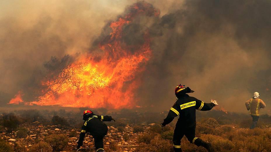 Bombeiros tentam conter incêndio florestal em Marathon, perto de Atenas. Os fortes ventos alastraram o fogo, danificando casas