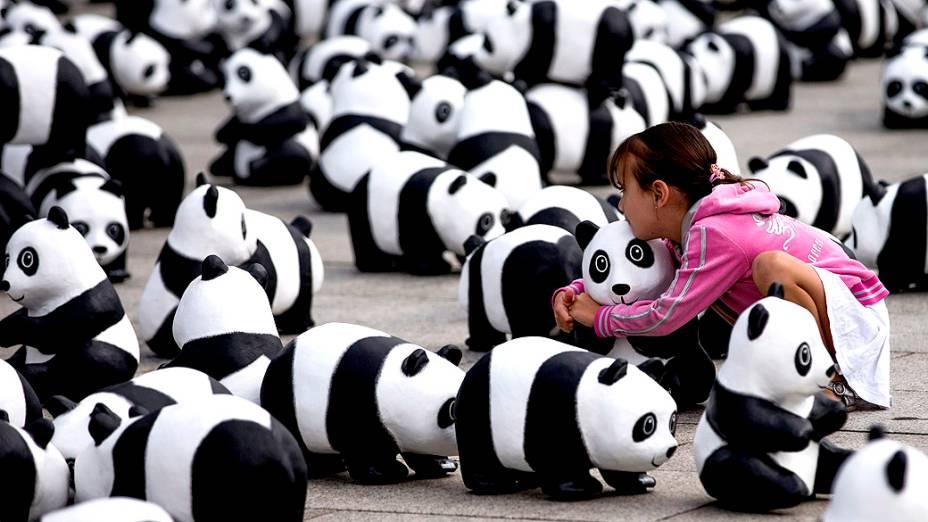 Uma criança abraça uma escultura de panda nesta segunda-feira (5). A organização de defesa do meio-ambiente WWF (World Wildlife Fund) espalhou 1600 figuras de pandas na frente da principal estação ferroviária de Berlim, na Alemanha, para celebrar seus 50 anos de existência e chamar atenção para espécies ameaçadas de extinção