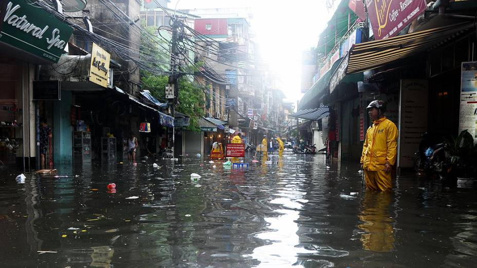 Trabalhadores do serviço ambiental municipal prestam socorro em uma rua inundada após um tufão atingir o centro de Hanói, trazendo fortes chuvas ao Vietnã