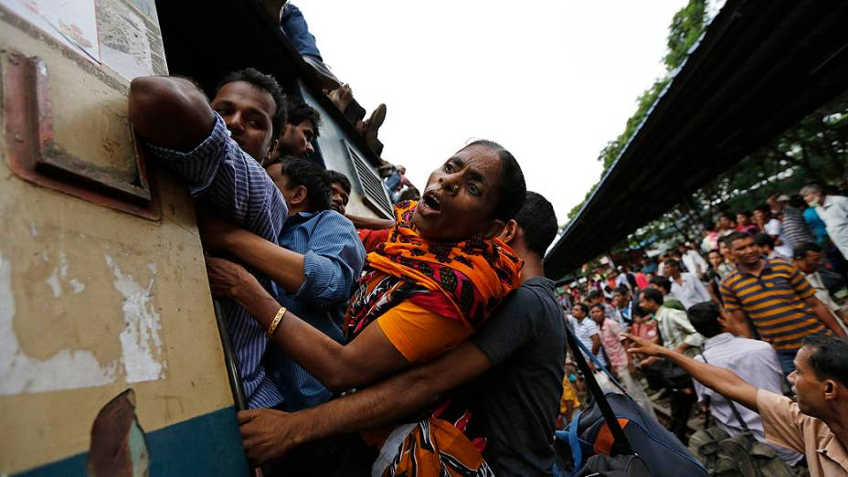Passageiros seguram-se na porta de um tremsuperlotadoem Dhaka. Milhões de moradores viajam à capital para celebrar o Eid al-Fitr, fim do mês de jejum do Ramadã, em Bangladesh