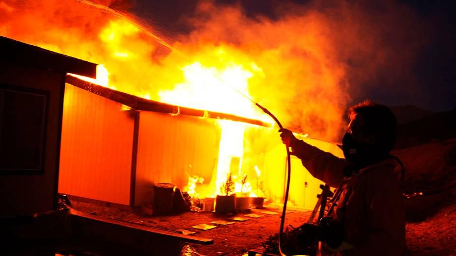 Homem usa mangueira para apagar fogo de uma casa em Banning, Califórnia. Um incêndio florestal, feriu dois bombeiros e um civil forçando a evacuação de centenas de moradores de três pequenas comunidades, nos Estados Unidos