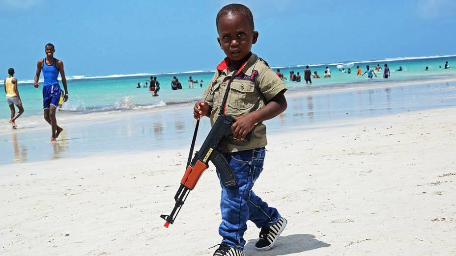 Menino anda com uma arma de brinquedo ao longo da Praia Lido, perto de Mogadíscio, na Somália