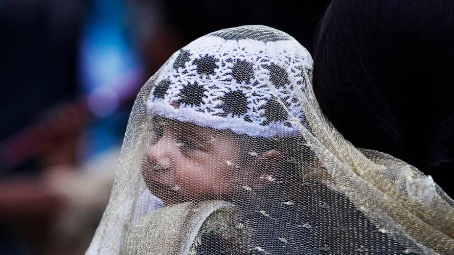Criança carregada pela mãe em um mercado na véspera do festival Eid al-Fitrque marca o fim do mês sagrado do Ramadã, em Srinagar, na Índia
