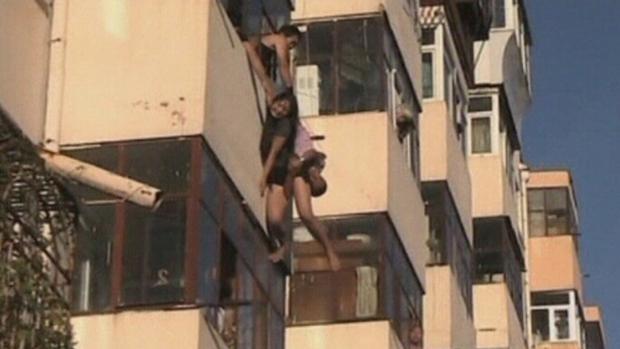 Imagem divulgada nesta segunda-feira (12), chinesa escorrega da sacada e namorado tenta resgatá-la. O casal foi retirado por vizinhos, em Harbin