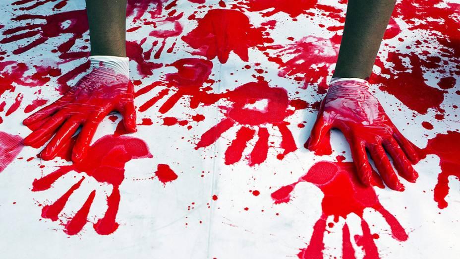 Manifestante com as mãos pintadas de vermelho durante protesto contra o plano de Israel para libertar 26 prisioneiros palestinos como um gesto de boa vontade para retomadadas negociações de paz , em frente ao Ministério da Defesa, em Tel Aviv