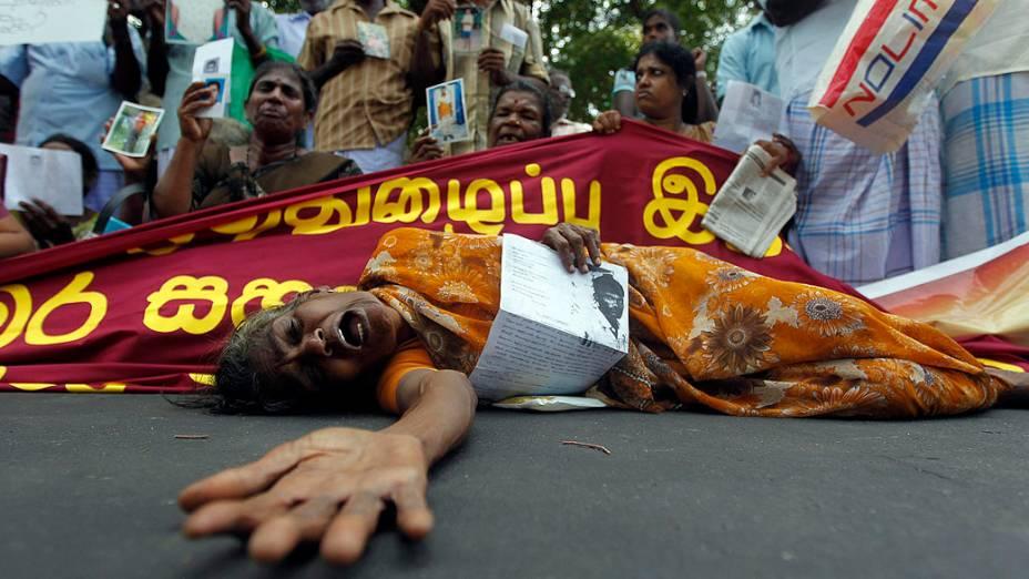 Mulher da etnia tâmil chora em protesto e segura imagem de membro da família que desapareceu durante guerra civil em Jaffna, no Sri Lanka