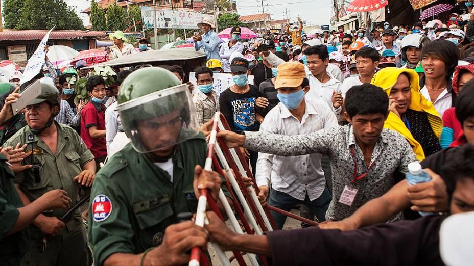 Trabalhadores da fábrica de vestuário atravessam um bloqueio da polícia durante um protesto em direção ao Ministério dos Assuntos Sociais para exigir um aumento dos salários, em Phnom Penh, Camboja