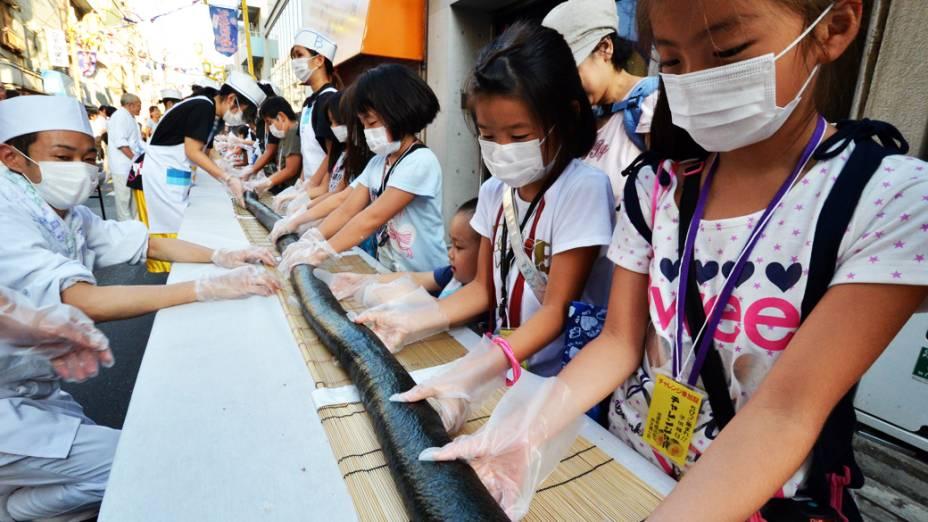 Crianças japonesas preparam sushi de 120 metros de comprimento em um festival de rua que acontece todos os anos durante o verão na capital, Tóquio