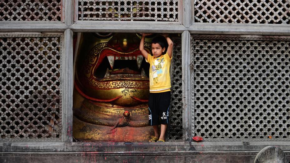 Criança fotografada ao lado de uma estátua de Swet Bharab, usada durante o festival Indra Jatra, em Katmandu, Nepal