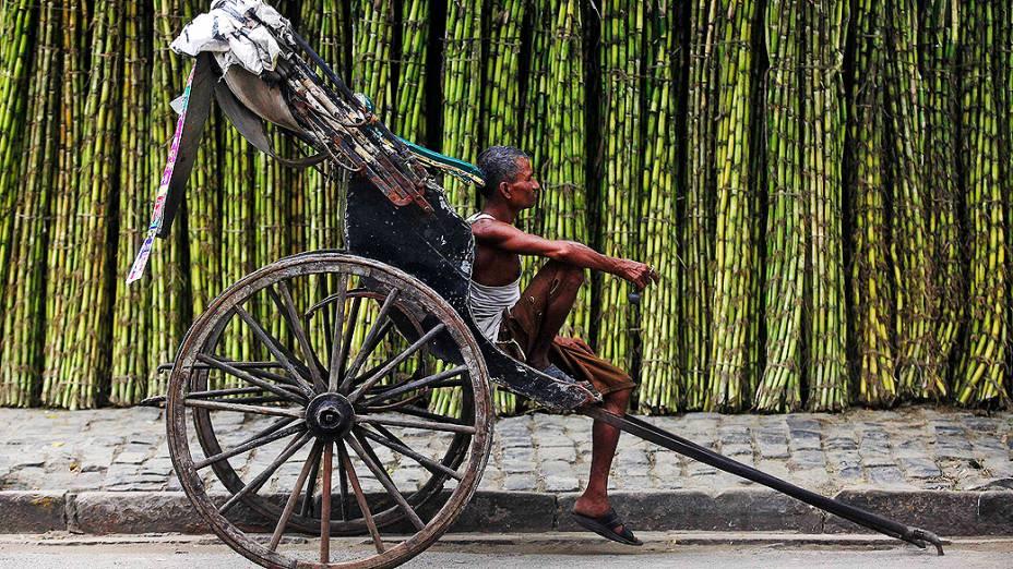 Puxador de riquixá à espera por clientes em um mercado de cana em uma estrada de Calcutá, na Índia, na segunda-feira (16)