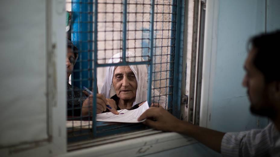 Mulher palestina espera para receber ajuda alimentar em um centro de distribuição de ajuda da ONU na Cidade de Gaza