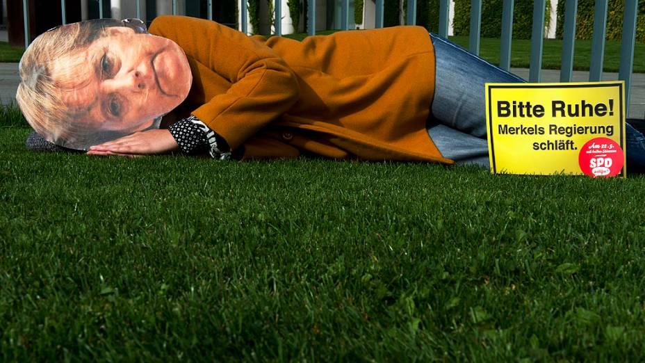 Manifestante do Partido Social Democrata (SPD) vestida como a chanceler alemã Angela Merkel deita em frente da Chancelaria em Berlim, com os dizeres Silêncio por favor! Governo de Merkel está dormindo, na Alemanha