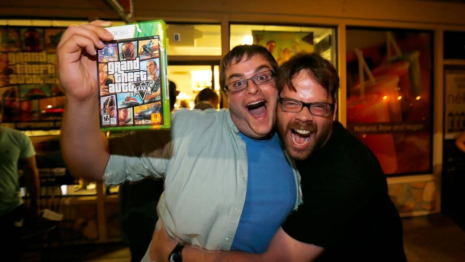 """Jogador comemora o lançamento do game """"GTA V"""" com Michael Petterson, um dos desenvolvedores do jogoem uma loja de jogos em Encinitas, Califórnia"""
